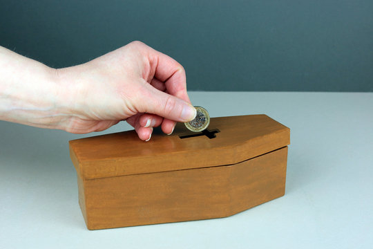A hand putting a pound coin in to a small coffin money box. Saving for funeral expenses concept.