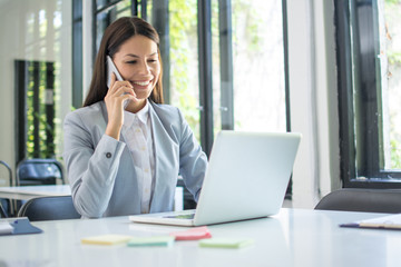 Businesswoman talking on the phone while working on laptop in office. Business concept.