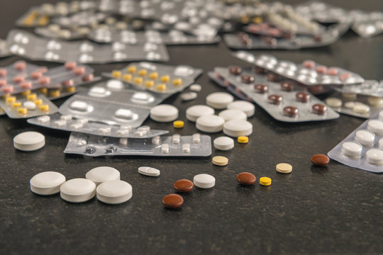 Various loose tablets and packaged medicines lie on a black table.
