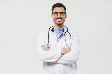 Portrait of smiling young male doctor with stethoscope around neck standing with crossed arms in white coat, isolated on gray background Fotobehang