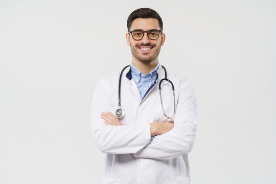 Portrait of smiling young male doctor with stethoscope around neck standing with crossed arms in white coat, isolated on gray background