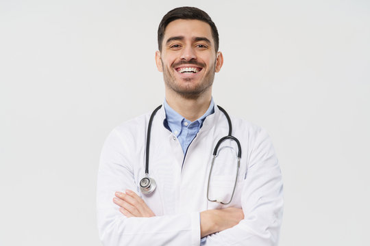 Close-up portrait of cheerful lauging young male doctor with stethoscope around neck, wearing white coat, isolated on gray background