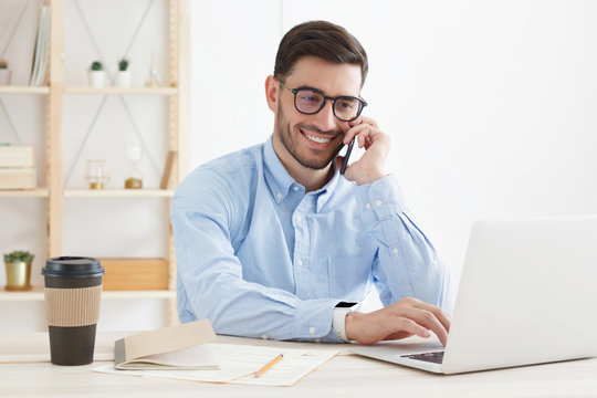 Young business man wearing glasses, working in office, looking attentively at screen, typing, answering phone call and consulting partner or client, smiling with confidence