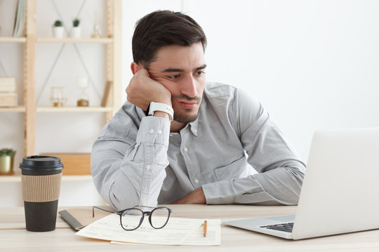 Business man in his office working on laptop, resting head on hand because he is tired, doing work overtime, stressed and bored