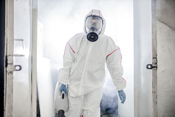 caucasian disinfector use sprayers and germs that adhere on objects on the surface, removing bacterias, preventing infection Covid 19 viruses or coronavirus and various pathogens Wall mural