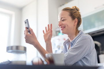 Young smiling cheerful woman indoors at home kitchen using social media on phone for video chatting and stying connected with her loved ones. Stay at home, social distancing lifestyle. Fotobehang