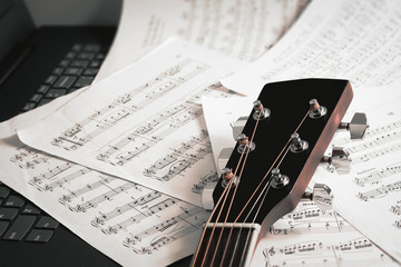close up of guitar neck and note sheet and notebook - selective focus