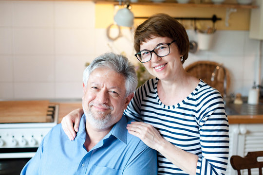 Happy senior couple stay at home. Middle aged man and woman hugging and smiling in cozy kitchen inside. Concept of family love, wellbeing, happiness, male and female health, enjoying retirement.