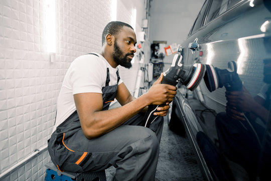 Auto detailing service, polishing of the car. Side view of young African American man worker n t-shirt and overalls, polishing blue car door with orbital polisher
