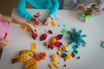 kids making origami crafts with paper, learning activities