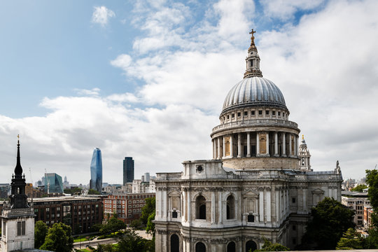 Side view of St. Paul's Cathedral in London against a cloudy sky, with some modern skyscrapers in the background.