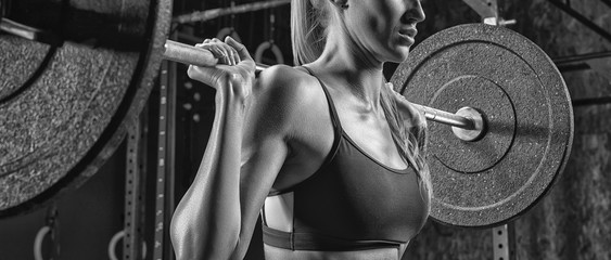 Sporty girl is preparing to do barbell squats in a gym Black and white wide close-up cover concept