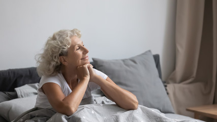 Peaceful calm positive middle aged senior retired woman sitting in bed after wakeup in weekend morning, enjoying good mood after good night rest relaxation, welcoming new day alone in bedroom. Wall mural