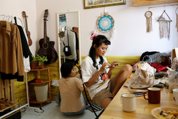 Nhu (L), 23, and Thanh, 21, put on make up to take pictures for their Instagram and Tik Tok pages as they stay home during the outbreak of the coronavirus diease (COVID-19), in Ho Chi Minh, Vietnam