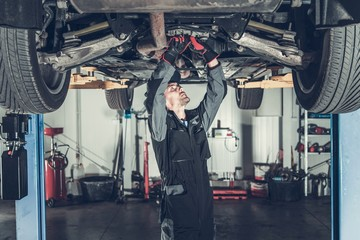 Obraz Mechanic Fixing Car on a Lift - fototapety do salonu