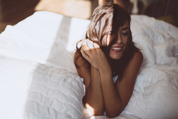 A beautiful young girl in the morning in a white bed after waking up, smiles at the new day and the sun from the window and covers her face with hair. Soft selective focus. Toned photo. Fotomurales
