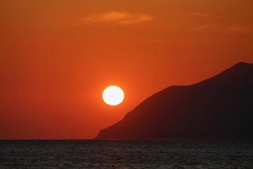 Photo sur Aluminium Rouge traffic coucher de soleil en crête en bord de mer avec un ciel rouge et des falaises