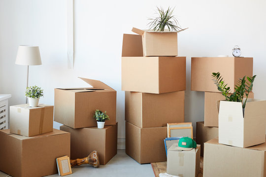 Background image of cardboard boxes stacked in empty room with plants and personal belongings inside, moving or relocation concept, copy space