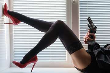 long legs in black stockings and red shoes and a revolver in hands on a window sill by the window with shutters