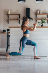 Fit woman exercising at home doing lunges exercise.