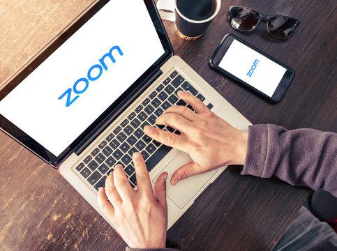 Laptop and mobile phone showing Zoom Cloud Meetings app logo. Antalya, TURKEY - March 30, 2020.