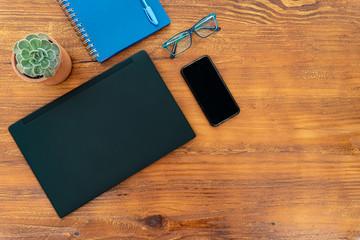 Escritorio de madera con computador, gafas, teléfono celular, cuaderno, lapicero y planta
