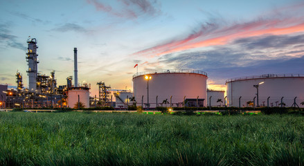 Oil and gas industry, oil refinery industry, refinery form factories, oil storage tanks and steel pipes with sunset background