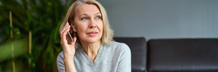 Beautiful mature blond woman talking on mobile phone at sofa. Fotomurales