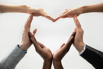 Close up bottom view concept of diverse business people join hands forming heart. Show unity and support, protection of business. Multiracial colleagues involved in team building activity for charity.