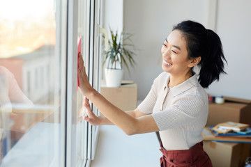 Waist up portrait of young Asian woman washing windows while enjoying Spring cleaning in house or apartment, copy space