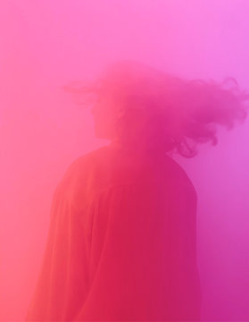 Woman surrounded by pink smoke