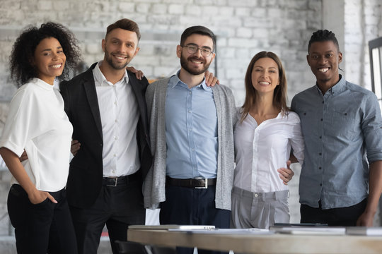 Portrait of standing in row smiling multiracial team embracing looking at camera. Happy diverse corporate staff, hugging specialists, bank workers photo shoot, HR agency recruitments.