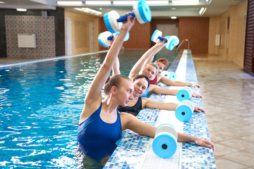 Young girls and middle-aged women do aqua aerobics with dumbbells in a swimming pool with a trainer, fitness exercises for weight loss in water