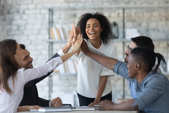 Excited successful african american businesswoman with multiracial business people giving high five, celebrating win. Happy employees team engaged in team building activity at corporate meeting.