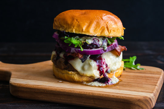 Red, White, and Blueberry Bacon Burger with Basil Aioli: Bacon cheeseburger topped with Havarti cheese, blueberry compote, red onion, arugula, and basil aioli on a brioche bun