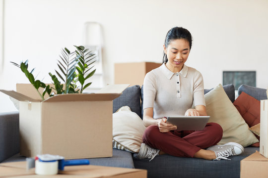 Full length portrait of modern Asian woman using digital tablet while unpacking boxes in new house or apartment, copy space
