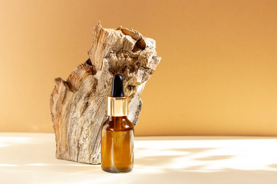 A glass cosmetic bottle with a dropper stands next to a bar of wood on a beige background with bright sunlight. The concept of natural cosmetics, natural essential oil