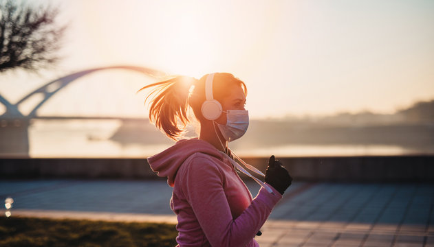 Beautiful young and fit woman in good shape running and jogging alone on city bridge street. She wearing protective face mask to protect herself from virus or allergy infection. Sunset in background.