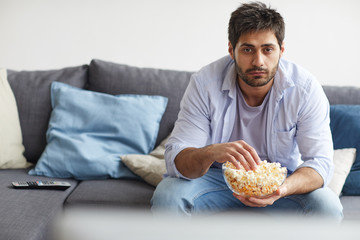 Portrait of sad bearded man watching TV and holding bowl of popcorn while sitting on sofa at home, copy space