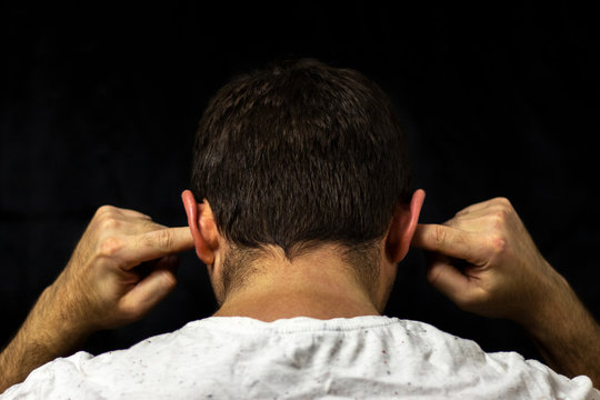 A man in a white T-shirt covers his ears with his fingers. Close up on black background. Back view.