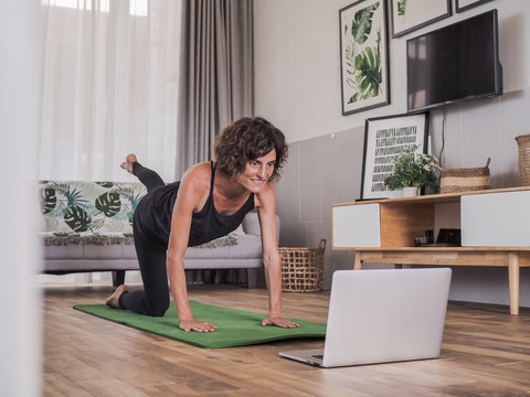 happy and smiling women looking into the laptop in doing a fitness pilates workout in her living room at home
