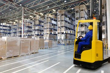 Huge distribution warehouse with high empty shelves and forklift with driver in yellow helmet.