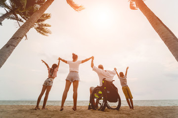 Disabled man in a wheelchair with his family on the beach. Silhouettes at sunset