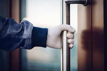 Hand in white latex glove holds handle while opening door. The concept of self-isolation during a pandemic and epidemic. Wall mural