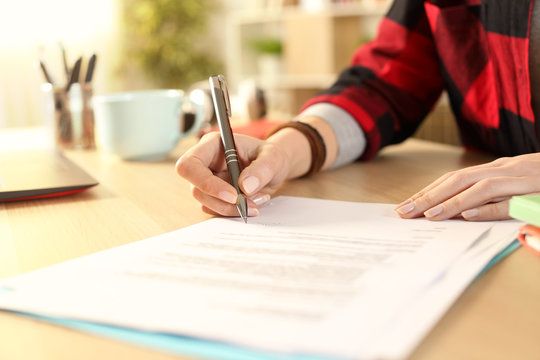 Student girl hands signing contract on a desk