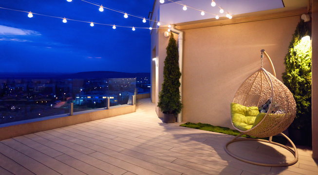cozy rooftop terrace with rattan hanging chair, garlands and beautiful landscape at night