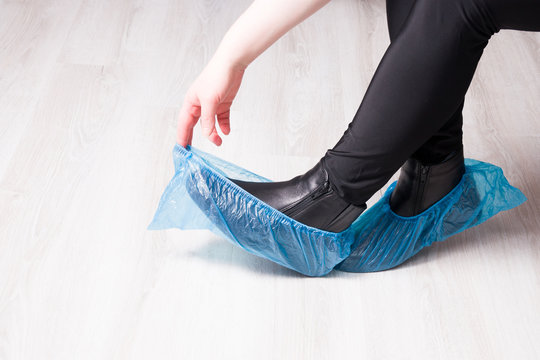 black leather boots in blue disposable shoe covers on a wooden light floor copy space, focus on boots