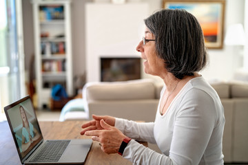 Adult  woman having video chat online on laptop with her granddaughter at home during quarantine isolation pandemic.  Senior lifestyle. Teacher giving online lesson to student from home. Fotomurales