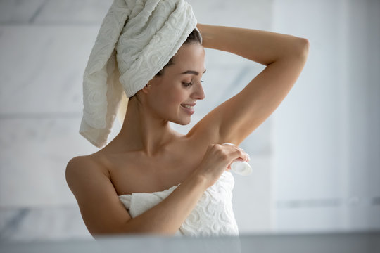 Millennial female wrapped in towel after shower use antiperspirant or deodorant after bath at home, young woman take care of armpit skin do daily beauty treatment in bathroom, hygiene concept