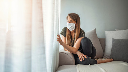 Sad lonely girl isolated stay at home in protective sterile medical mask on face looking at window, bored woman because of Chinese pandemic coronavirus virus covid-19. Quarantine, prevent infection